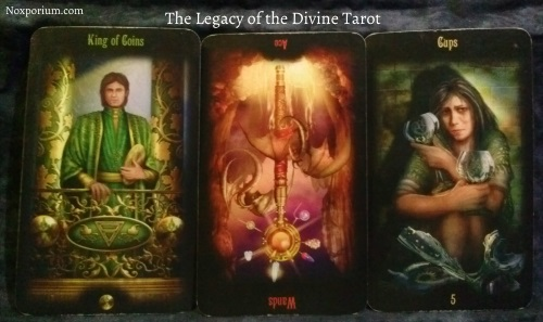 The Legacy of the Divine: King of Coins, Ace of Wands reversed, & 5 of Cups.