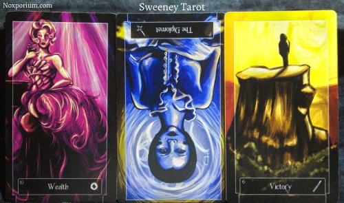 The Sweeney Tarot: 10 of Coins, Page of Swords reversed, & 6 of Wands.