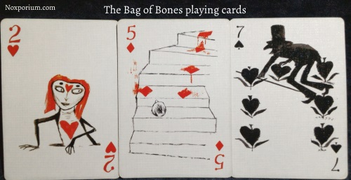 Bag of Bones playing cards: 2 of Hearts, 5 of Diamonds, & 7 of Spades.